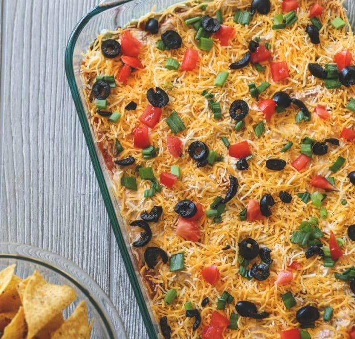 7 layer dip with cheese topped in black olive and tomatoes